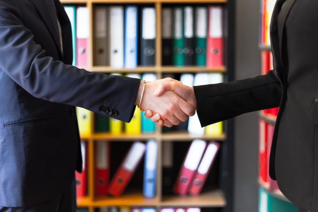 Lawyers shake hands as they agree to terms of over the luxury apartment.